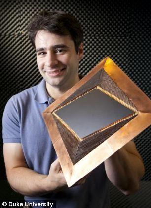杜克大学的研究员内森-兰迪展示新研制的隐形装置,首次让物体实现完美隐形